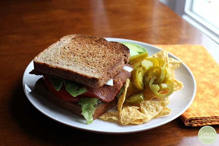 Vegan BLT with vegan meat, lettuce, and tomato on toasted wheat bread with chips.