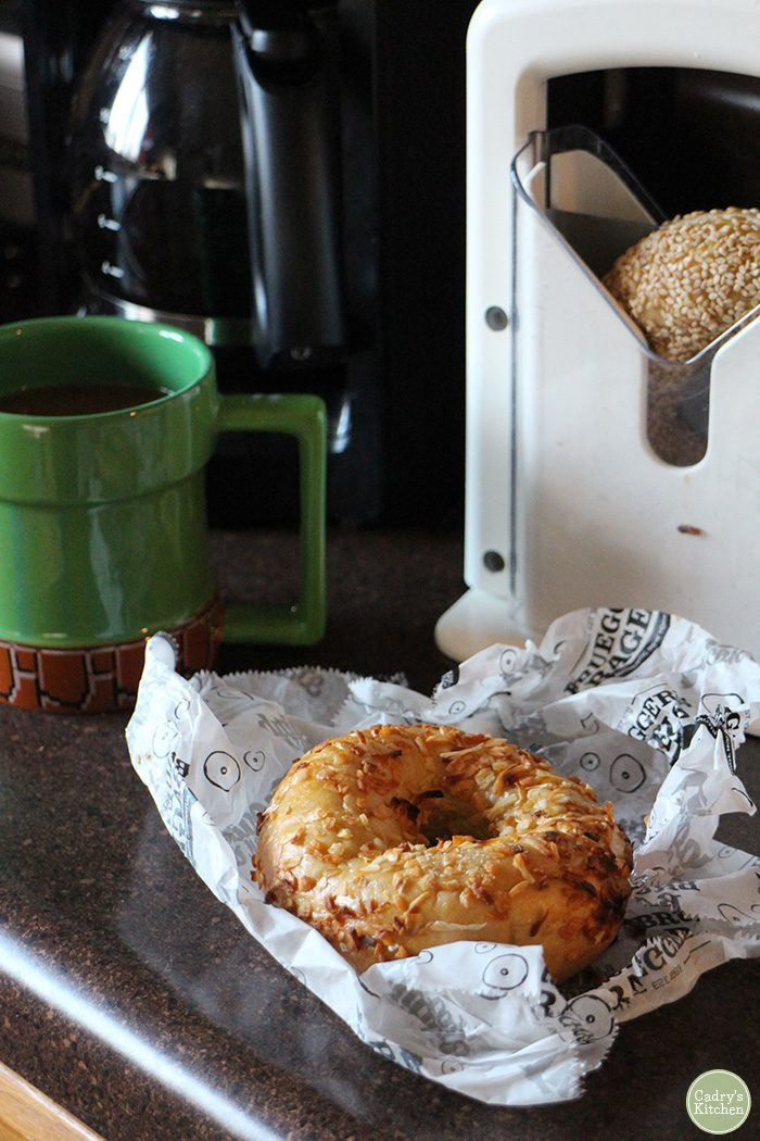 Bagel on paper by coffee cup & bagel slicer.