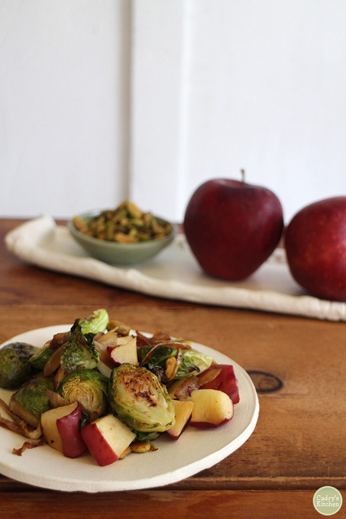 Roasted Brussels sprouts with apples, caramelized onions & pistachios. A vegan side dish that the whole family will love. Great for Thanksgiving! | cadryskitchen.com