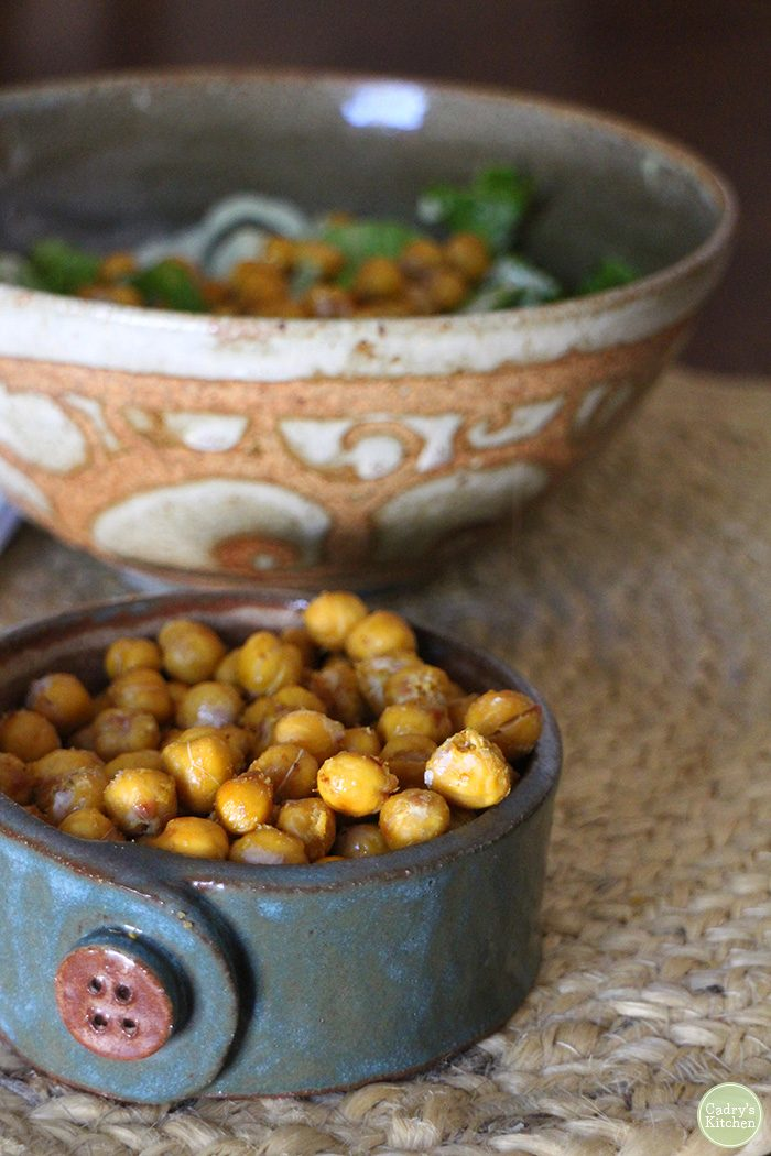 Roasted chickpeas in bowl with salad in background.