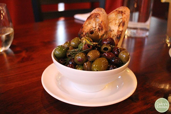 Warmed olives in bowl with bread.