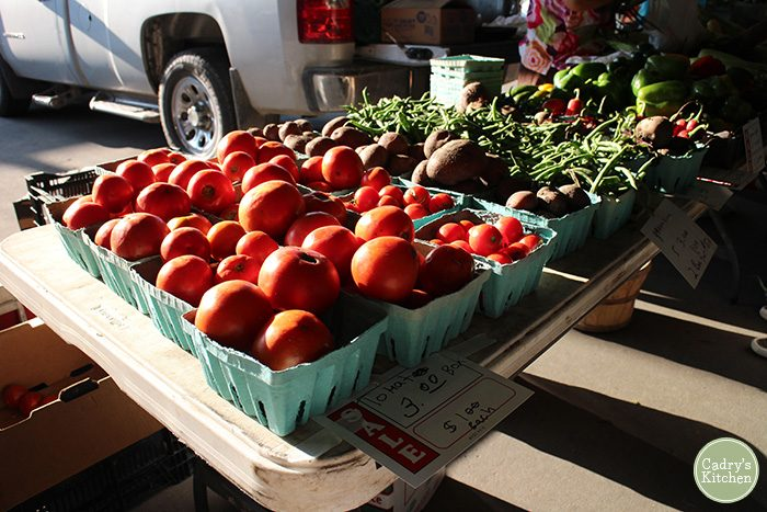 Tomatoes and beans on table at farmers market.