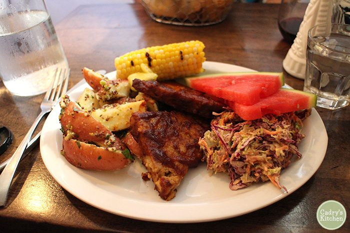 Barbecued seitan, corn on the cob, watermelon, and coleslaw at Modern Love Omaha.