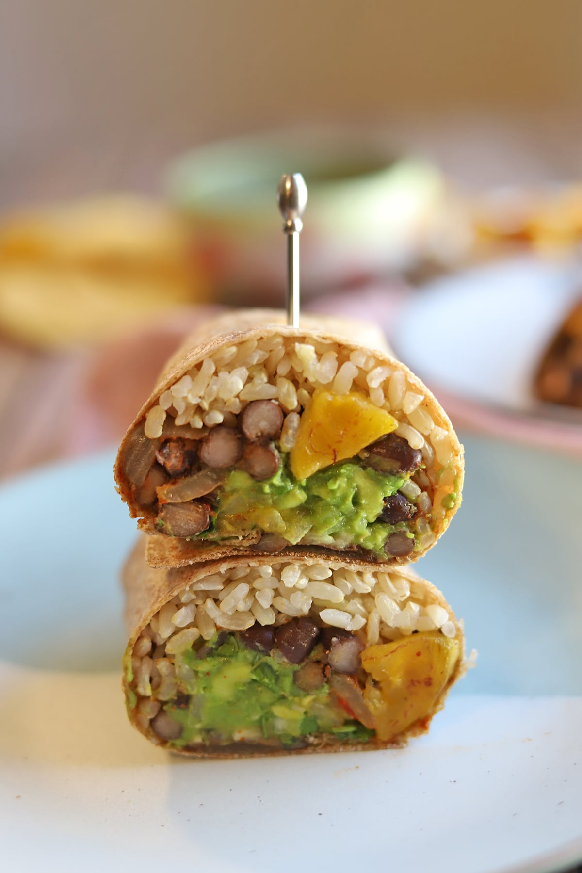 Black bean and rice burrito with plantains and guacamole on plate.