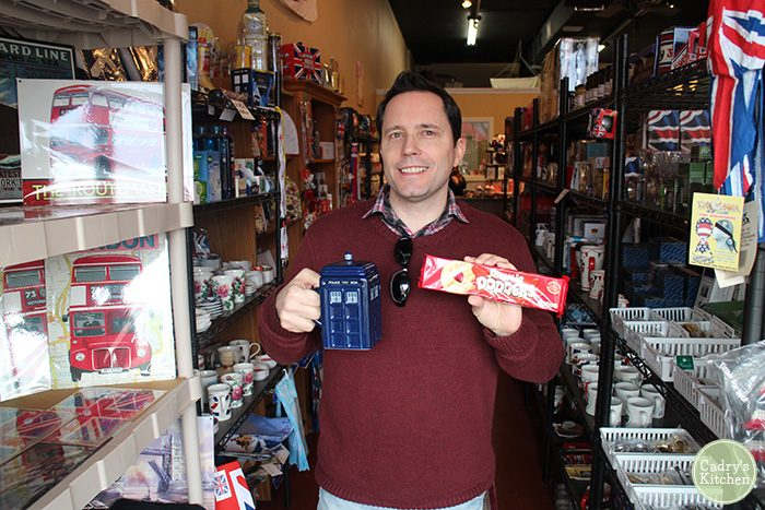 David holding Jammie Dodgers and TARDIS mug at British Shoppe.