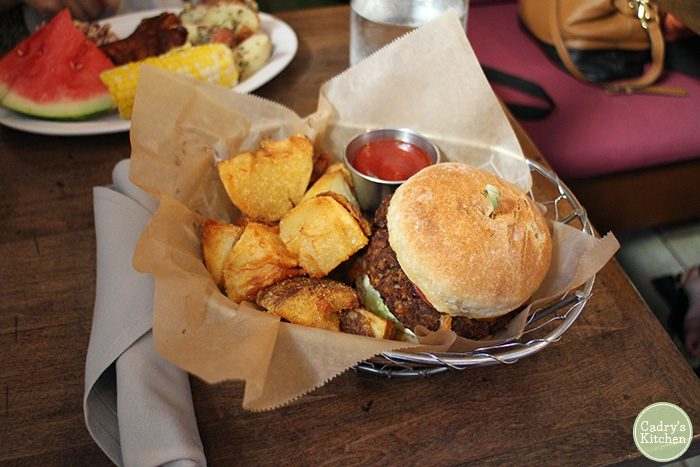 Burger and potato wedges in basket at Modern Love Omaha.