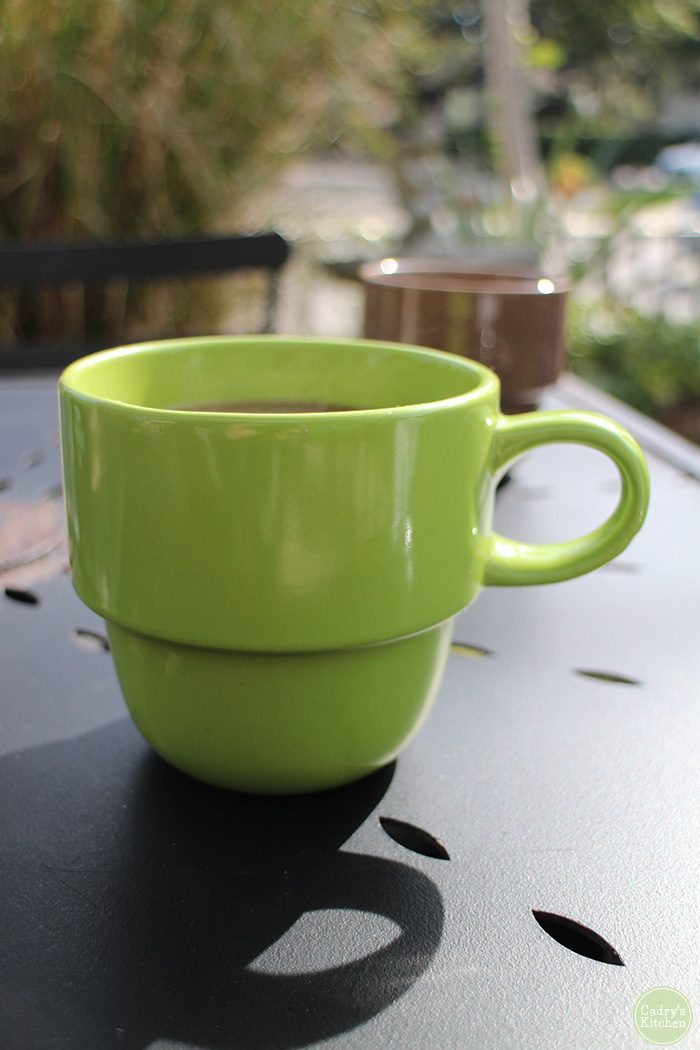 Green coffee cup on table, Dandelion Communitea Cafe