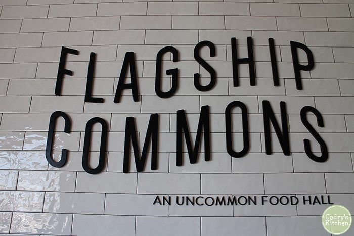 Subway tile wall that says Flagship Commons: An Uncommon Food Hall.