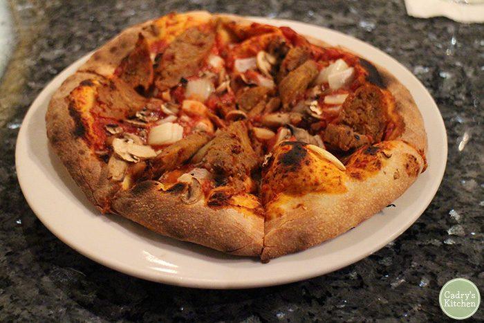 Mushroom and sausage pizza on plate.