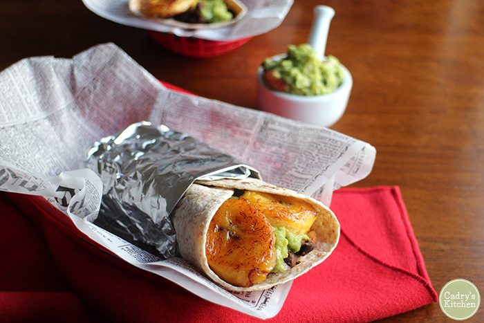 Burrito with plantains and guacamole wrapped in foil in paper lined basket.