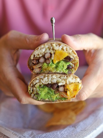 Hands holding black bean burrito with rice, plantains, and guacamole.