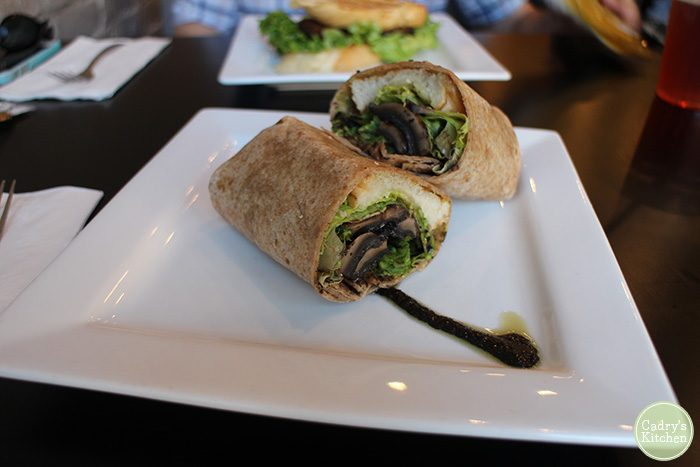 Mushroom sandwich wrap on plate with balsamic drizzle.