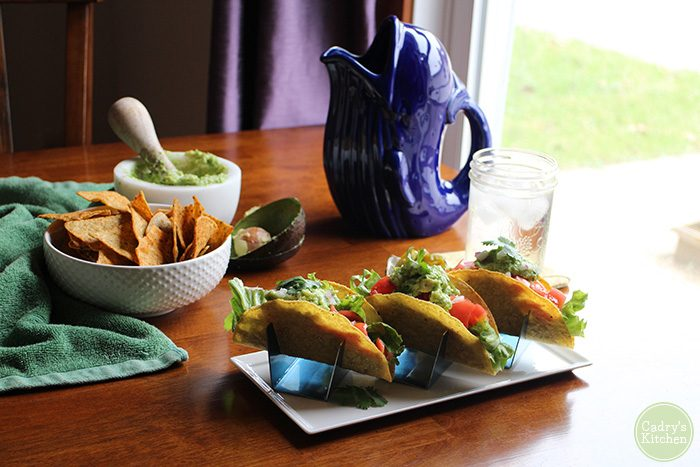 Black bean tacos on plate by bowl of chips and guacamole.