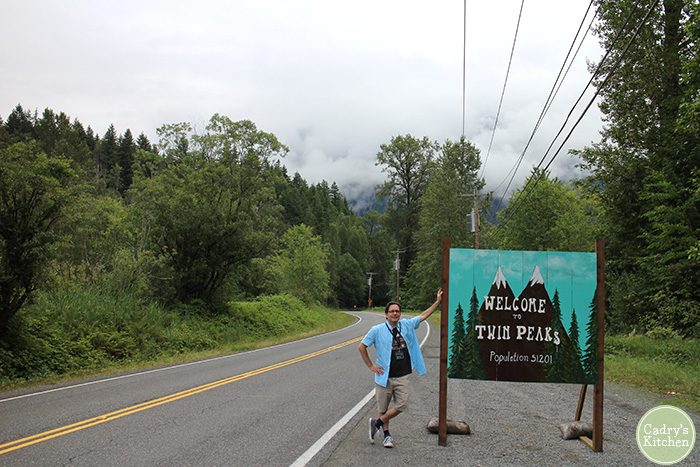 David posing by Welcome to Twin Peaks sign along road.