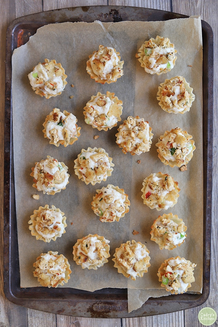 Overhead filo cups with cream cheese & chopped meatless crab on baking sheet.