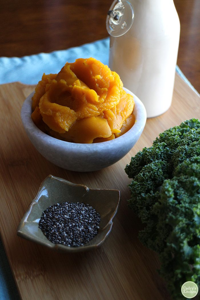 Canned pumpkin in bowl by chia seeds, kale, and non-dairy milk in bottle.