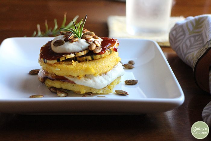 Fried vegan polenta with barbecued delicata squash and cashew cream in a stack on a plate.