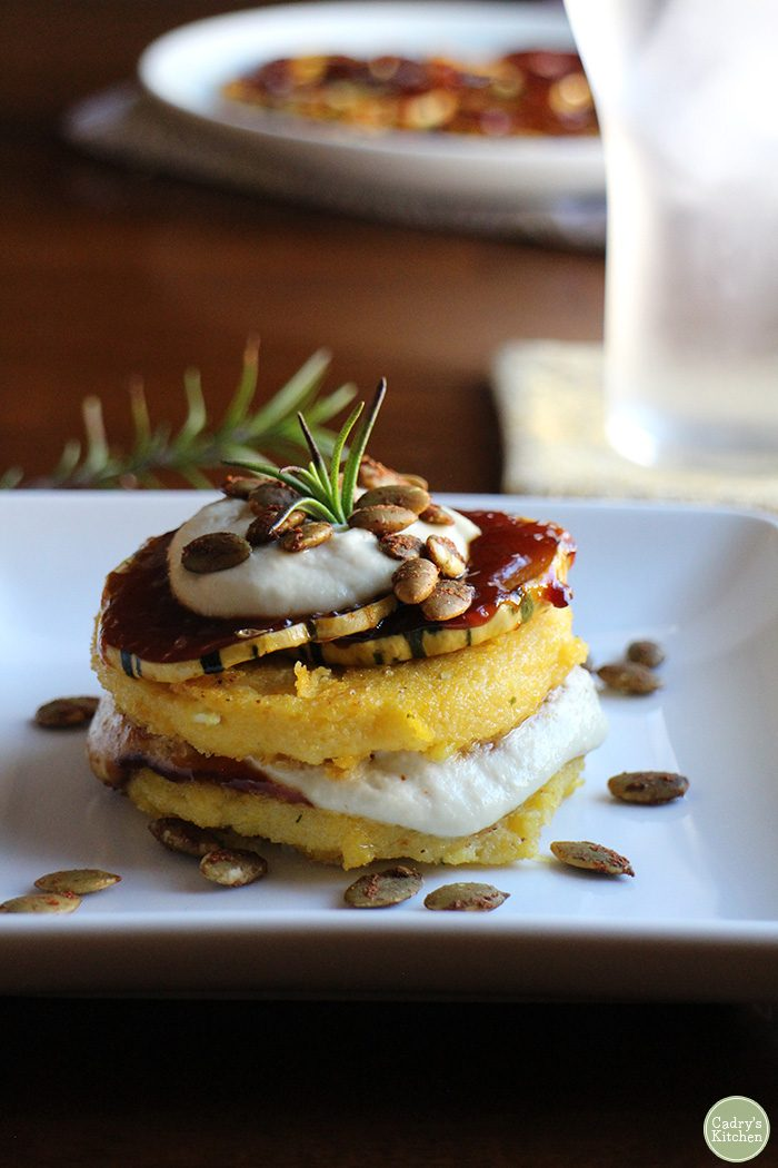 Polenta stack with barbecued squash and cashew cream on plate with pepitas.