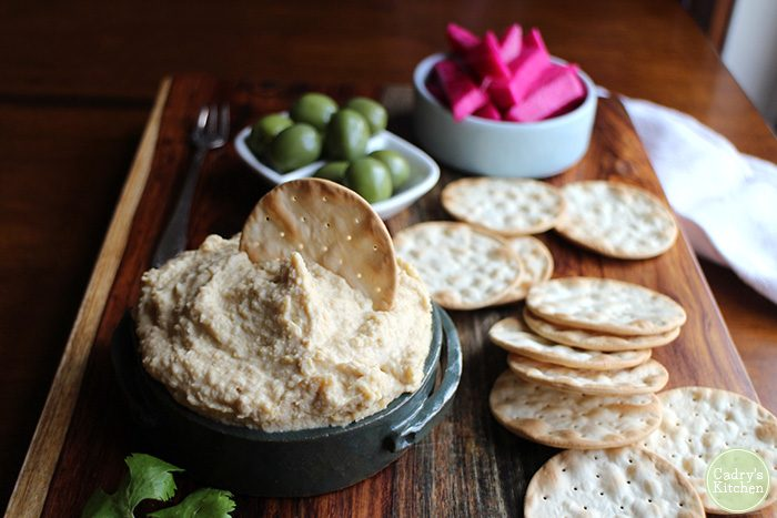 My favorite homemade hummus includes plenty of tahini, a splash of lemon juice, garlic, and the brine from the can of chickpeas to get its creaminess. Vegan. | cadryskitchen.com