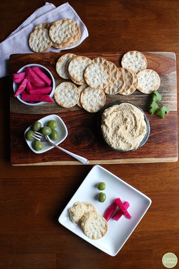 Homemade hummus with crackers, olives, and turnip pickles.