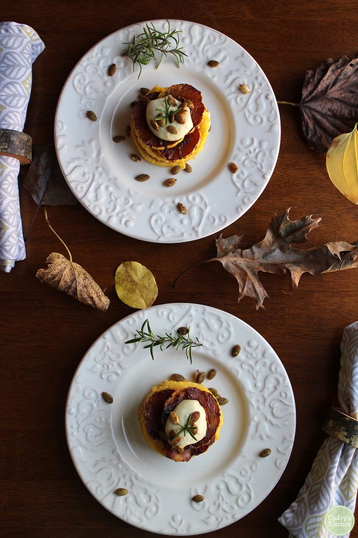 Polenta stacks on plates with bbq delicata squash and cashew cream.