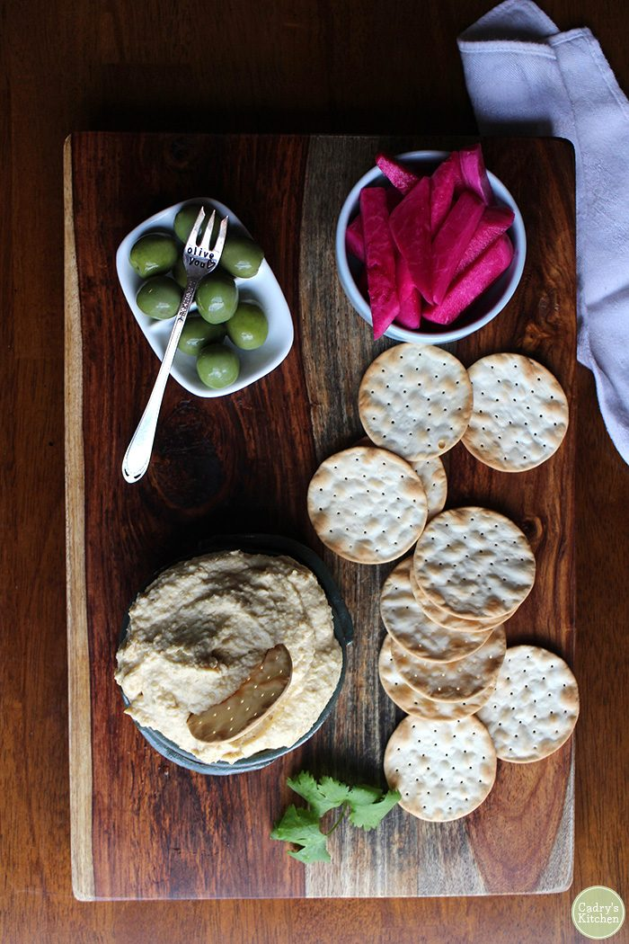 Homemade hummus with olives, crackers, and pickled turnips.