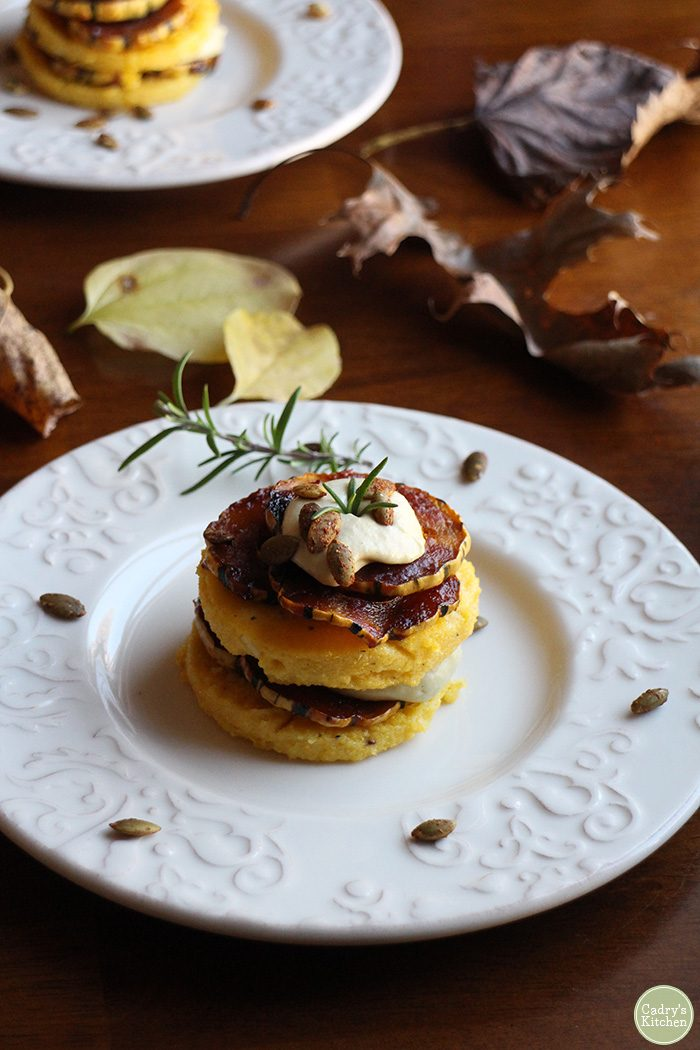 Stack of vegan polenta with cashew cream and barbecued delicata squash.