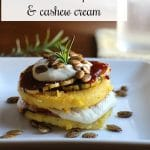 Text: Vegan polenta stacks with BBQ squash and cashew cream. Polenta stack on plate with pepitas.