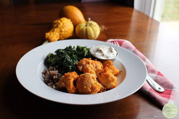 Buffalo cauliflower on plate with non-dairy blue cheese.