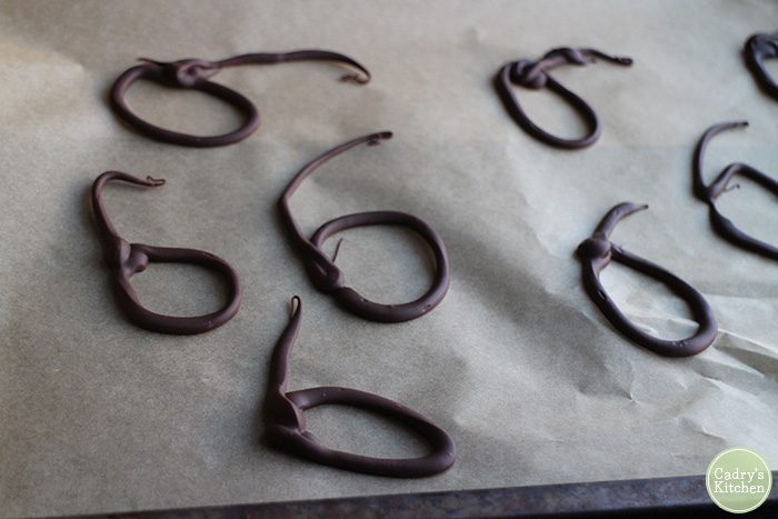 Chocolate lassos hardening on parchment paper.