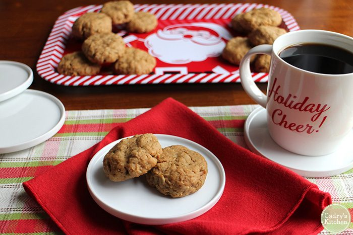 Peanut butter oatmeal cookies on plate with coffee in front of Santa tray.