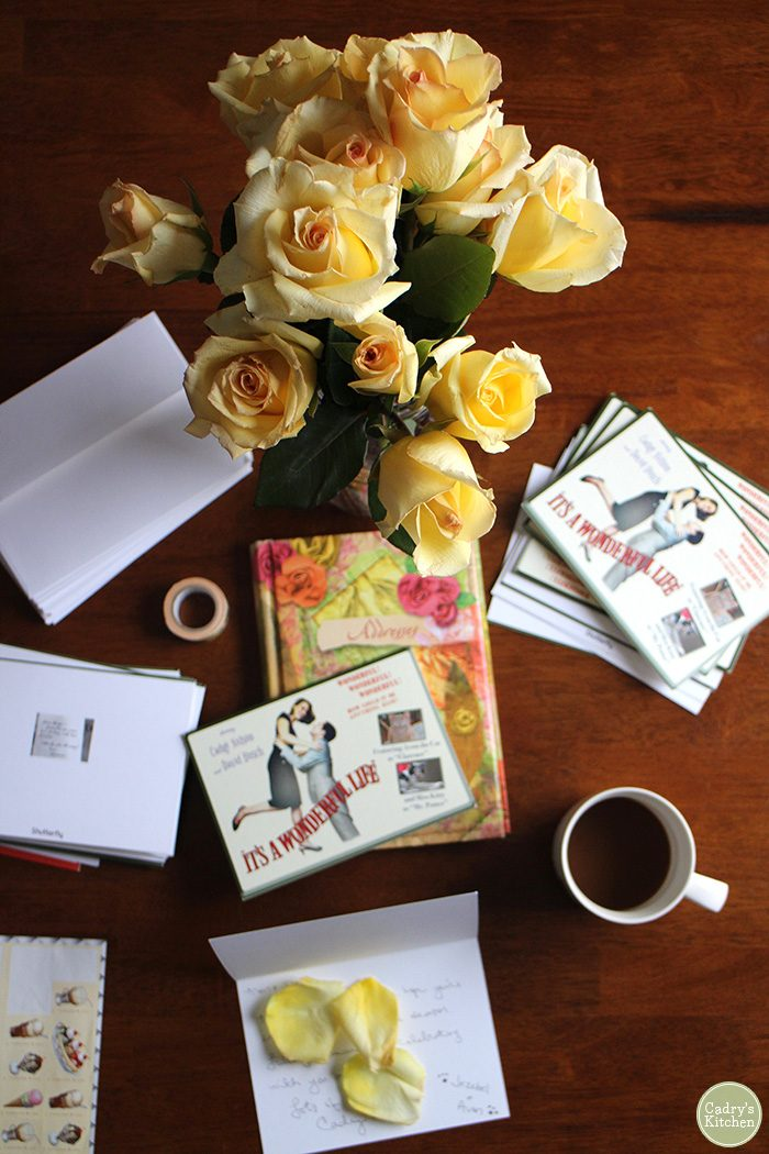Roses on table with stack of Christmas cards, address book, and coffee.