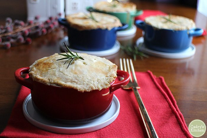 Mini vegetable pot pies on table with red napkin & gold fork.