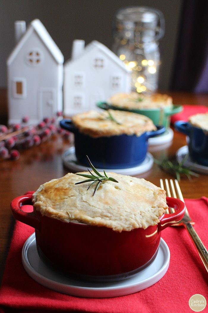 Mini pot pie in Le Creuset cocottes. Ceramic houses and lights in background.
