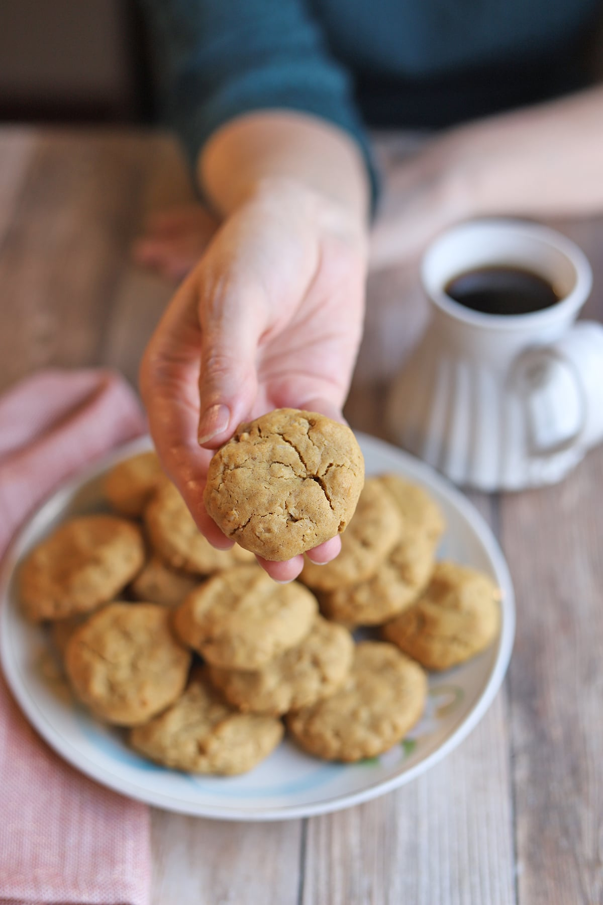 Hand holding cookie over platter & cup of coffee.