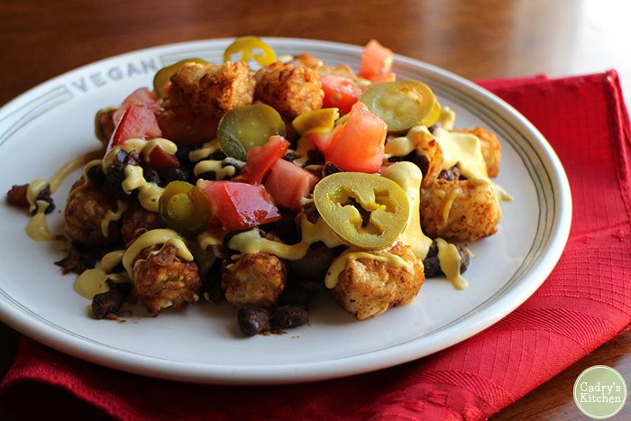 Totchos on plate with queso, tomatoes, and jalapeno peppers.