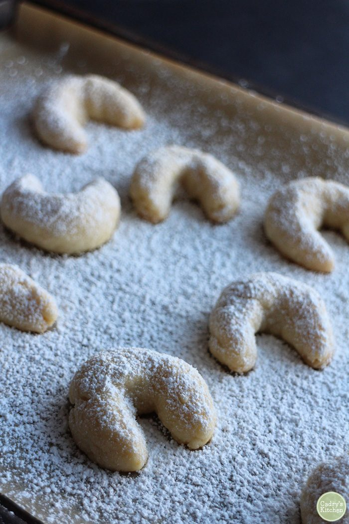 Moon cookies on parchment paper, covered in powdered sugar.