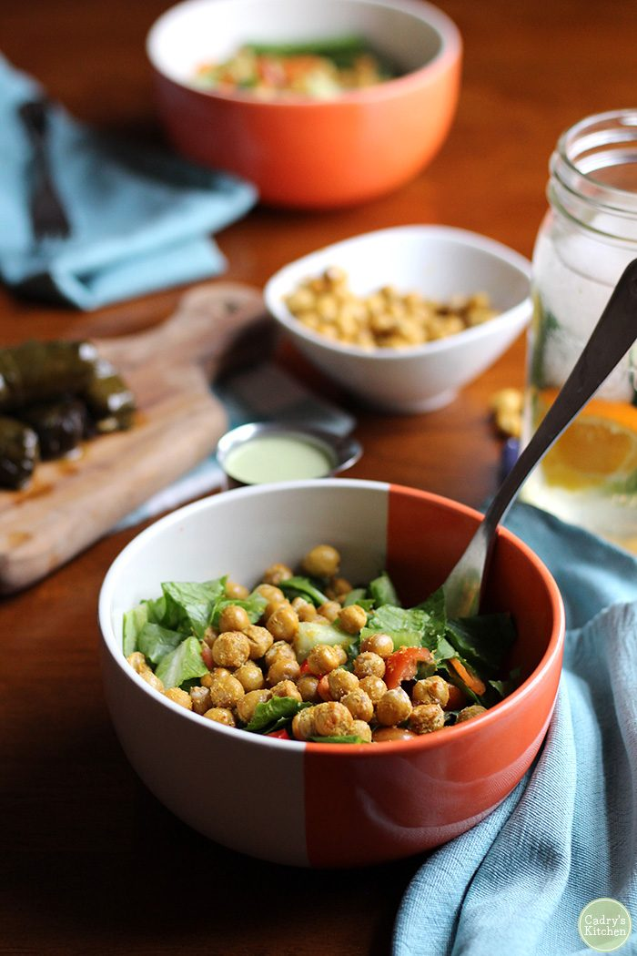 Salad with fried chickpeas, water, dolmas, and blue napkins on table.