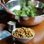 Roasted chickpeas in bowl in front of salad bowl.