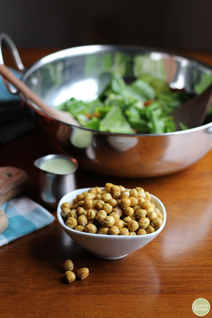 Small bowl of air fried chickpeas with romaine lettuce salad and dressing.