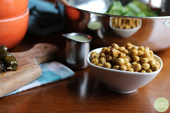Bowl of fried chickpeas on table next to metal salad bowl.