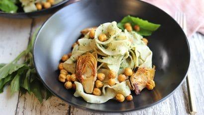 Bowl of vegan pesto pasta with artichokes.