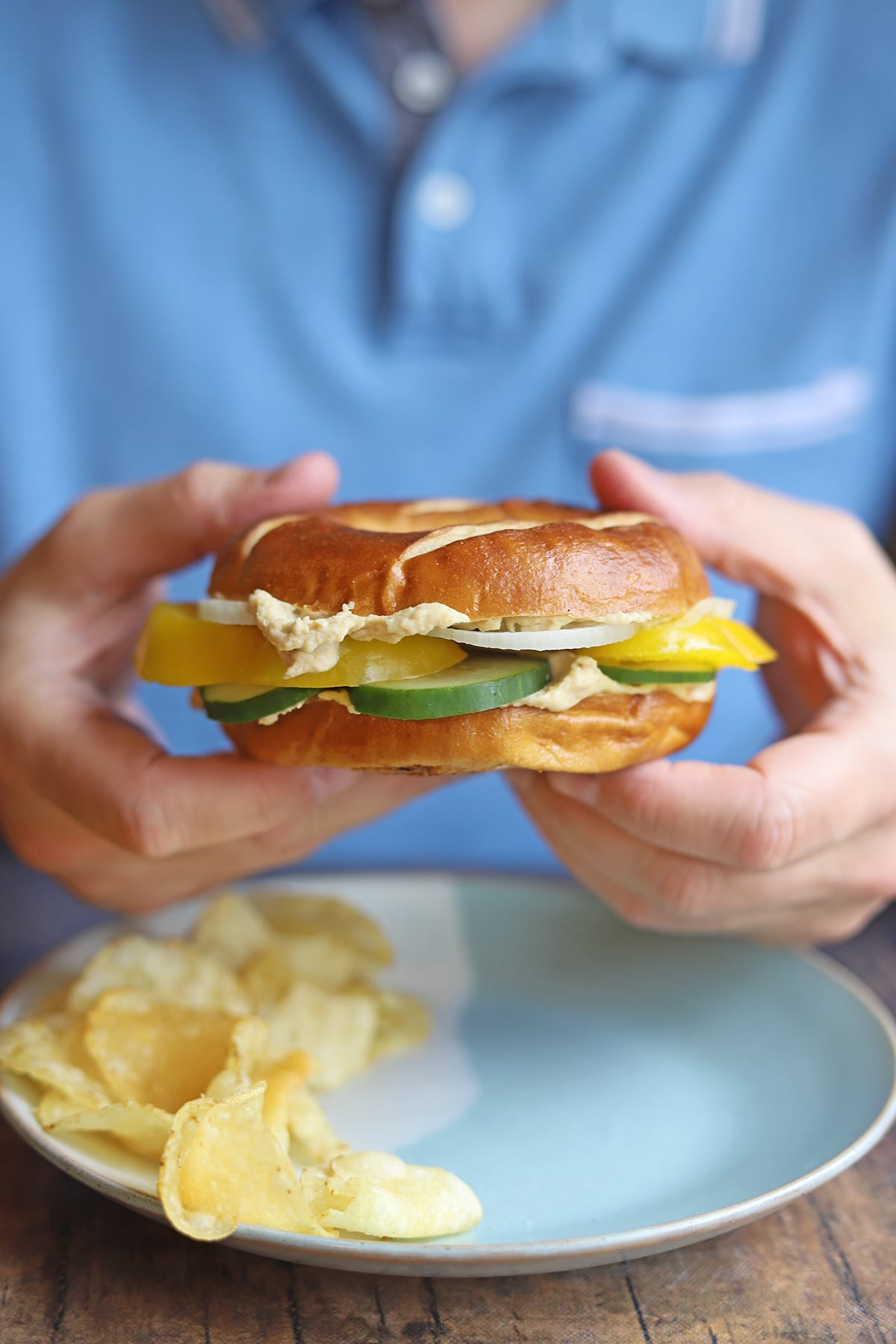 Hands holding bagel sandwich over plate.