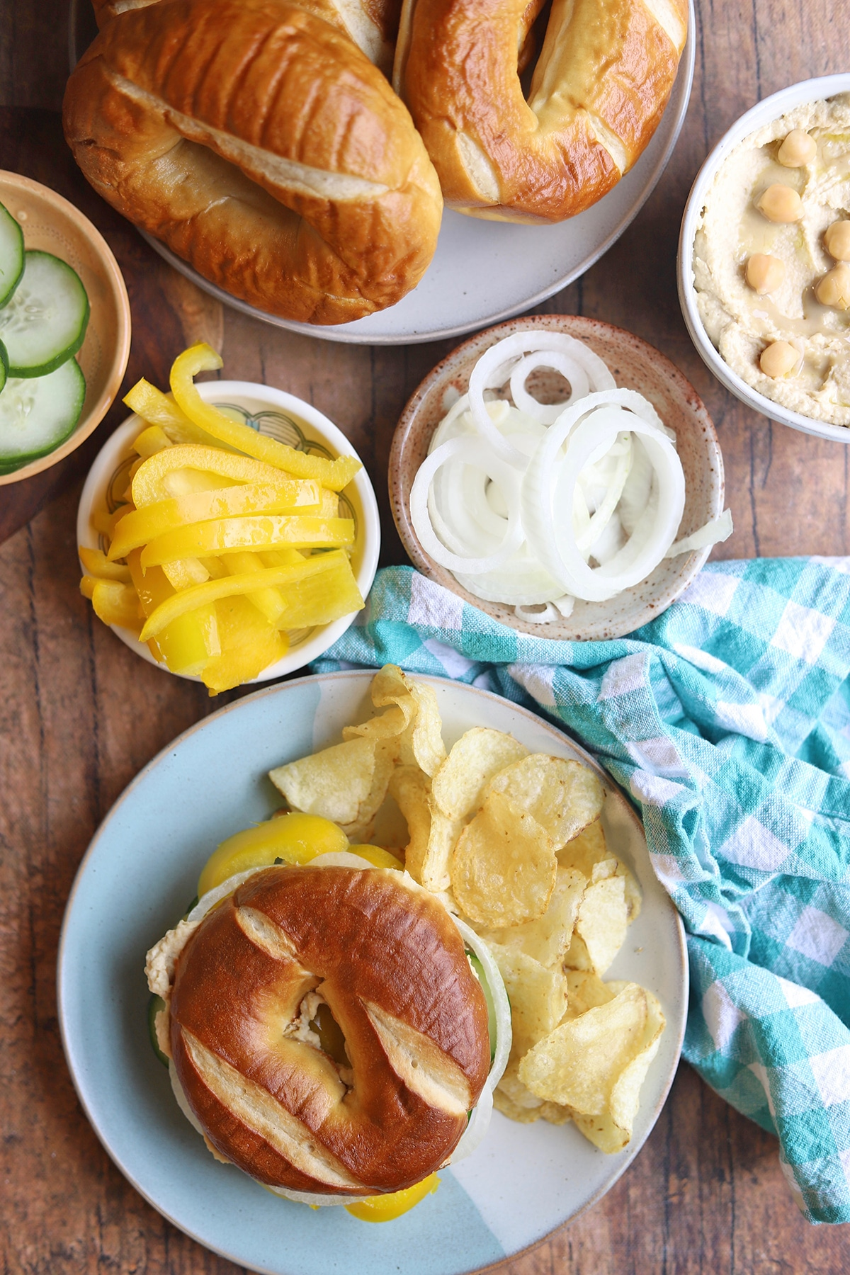Table with bagel sandwich, potato chips, and ingredients.