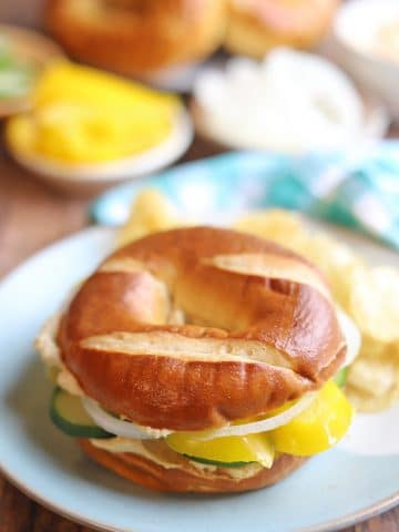 Bagel sandwich on table with potato chips.
