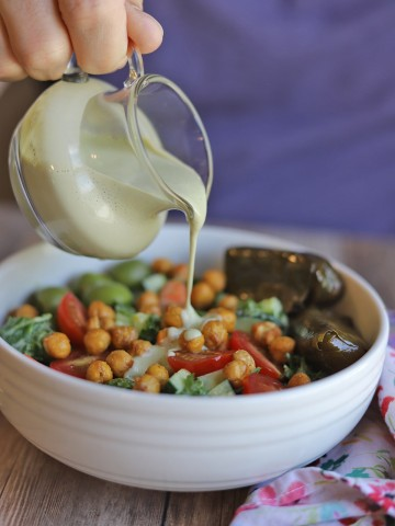 Creamy cashew dressing being poured onto kale salad.
