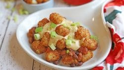Tater tots on platter with cashew queso and chili.