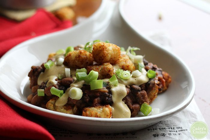 Vegan chili cheese tater tots: These mouthwatering and indulgent tots are topped with 3 bean chili, cashew queso, and a sprinkling of spring onions. A delicious dish for the big game or a handy way to repurpose leftovers. | cadryskitchen.com