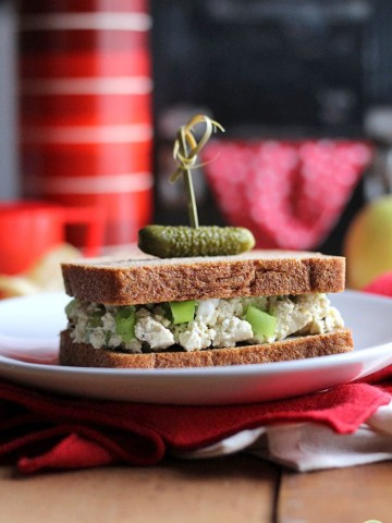 Close-up tofu salad sandwich on plate with pickle on top.