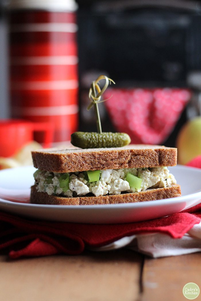 Vegan egg salad sandwich on plate with pickle.